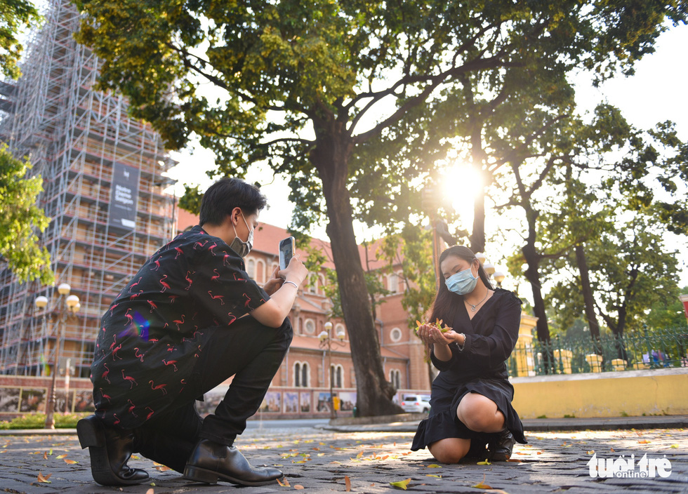 A man takes a picture of a woman with cho nau seeds near the Notre-DameCathedral BasilicaofSaigon in District 1. Photo: Ngoc Phuong / Tuoi Tre