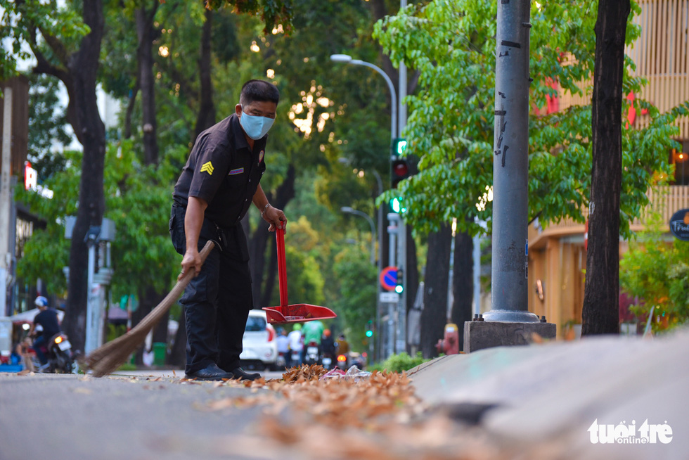 Nguyen Van Hoang, a security guard at a restaurant on Le Quy Don Street in District 3, sweeps cho nau seeds from the street. Photo: