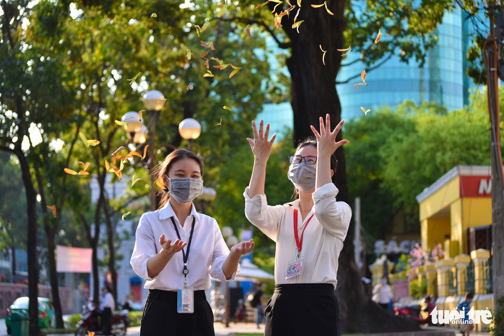 Two women throw cho nau (Dipterocarpus retusus) seeds and watch them float down in downtown Ho Chi Minh City. Photo: Ngoc Phuong / Tuoi Tre