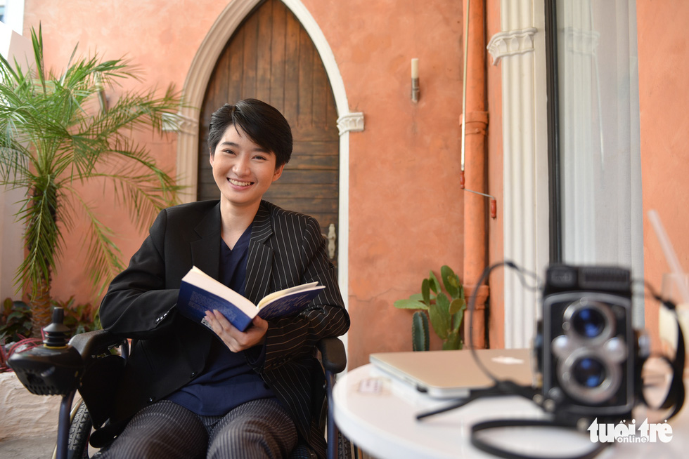 Le Phuong Uyen smiles while holding an open book in her hands. Photo: Ngoc Phuong / Tuoi Tre