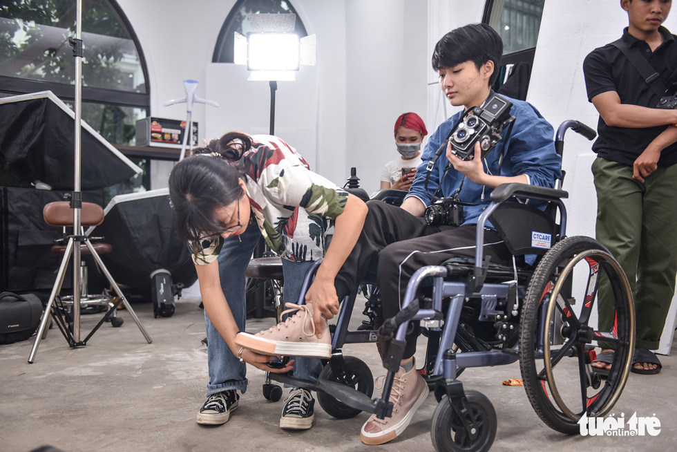 Mai Anh, a coworker, helps Uyen to put the foot in the right position that will make Uyen more comfortable. Photo: Ngoc Phuong / Tuoi Tre