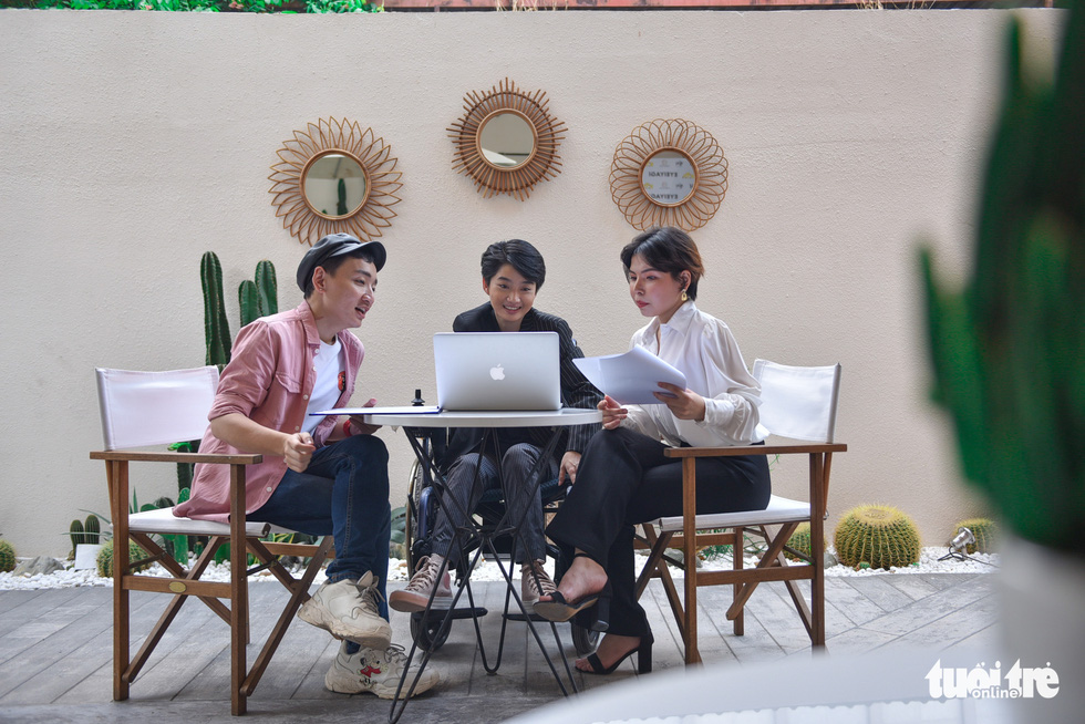 Pham Dac Mai Chi (outer right) and Tran Minh Chanh (outer left) are Le Phuong Uyen (center) look at the laptop screen while they are working together. Photo: Ngoc Phuong / Tuoi Tre