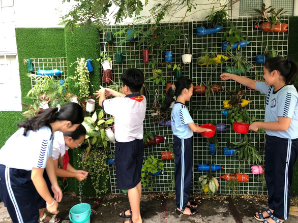 Students of Phu Tho Hoa Primary School water the hanging garden with pots made from used plastic bottles. – Photo: CK/Tuoi Tre