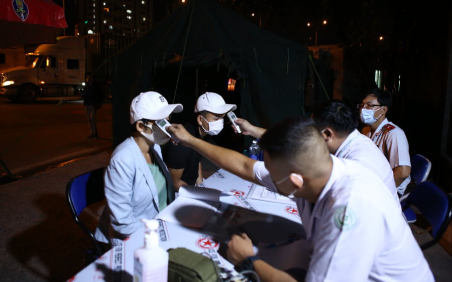 Medical workers measure people's body temperature at a checkpoint at a gateway to Ho Chi Minh City, May 15, 2021. Photo: Nhat Thinh / Tuoi Tre