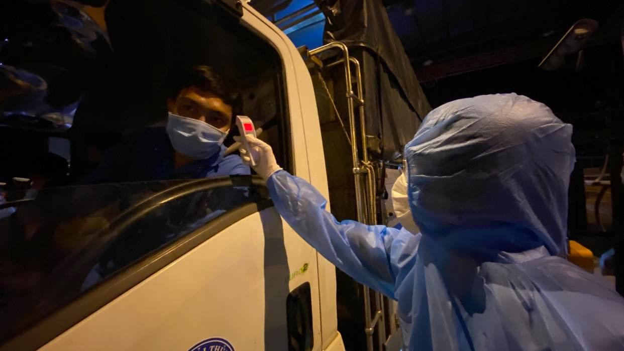 A medical workers measures a driver's body temperature at a checkpoint at a gateway to Ho Chi Minh City, May 15, 2021. Photo: Tu Trung / Tuoi Tre