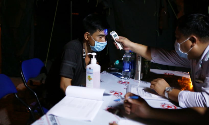A medical worker measures a man's body temperature at a checkpoint at a gateway to Ho Chi Minh City, May 15, 2021. Photo: Nhat Thinh / Tuoi Tre