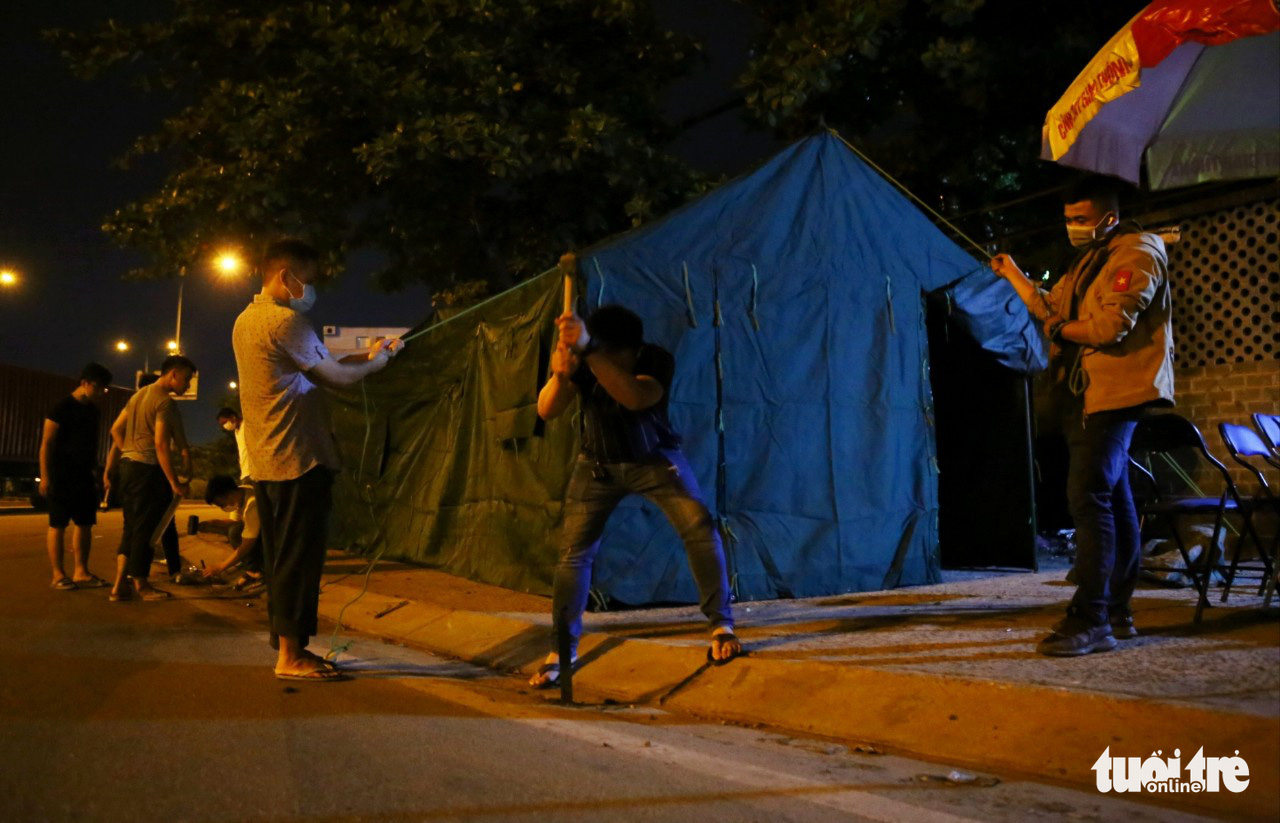 Staff put up a tent at a checkpoint at a gateway to Ho Chi Minh City, May 14, 2021. Photo: Nhat Thinh / Tuoi Tre