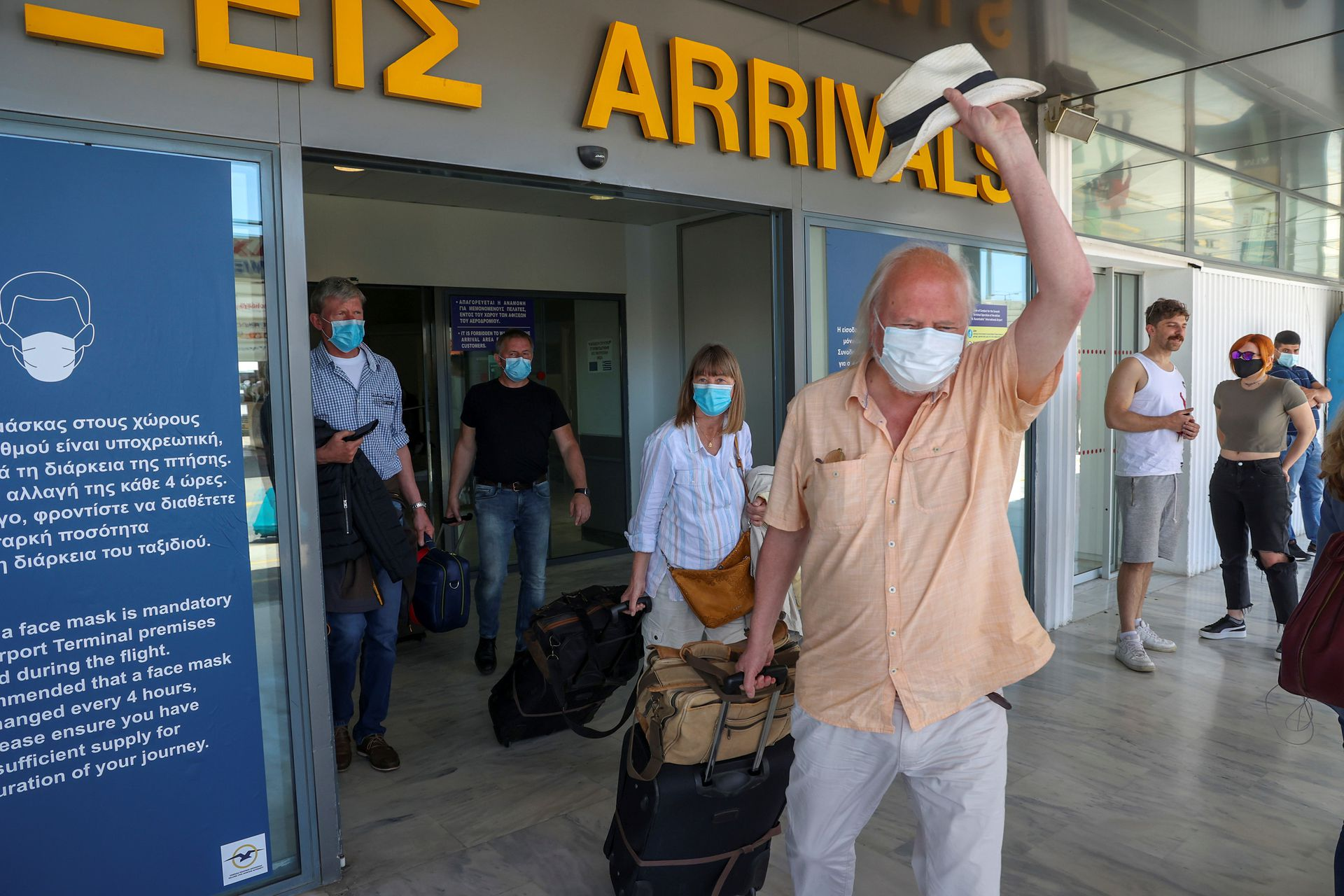 A man waves his hat as passengers arriving from Germany and Switzerland exit the terminal of the Heraklion airport, as the country's tourism season officially opens, on the island of Crete, Greece, May 15, 2021. Photo: Reuters