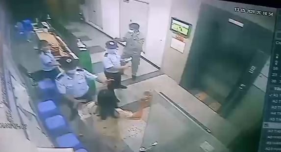 A woman is about to attack a security guard with a slipper at an apartment building in this screenshot taken from CCTV footage.