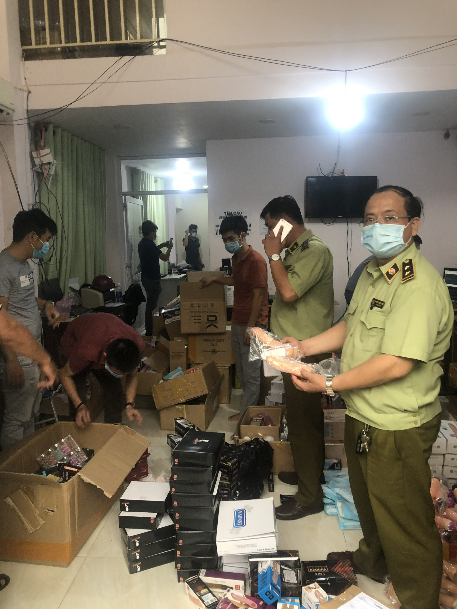 Market watchdog officers examine sexual wellness products of unknown origin at a warehouse in Ho Chi Minh City, May 15, 2021 in this supplied photo.