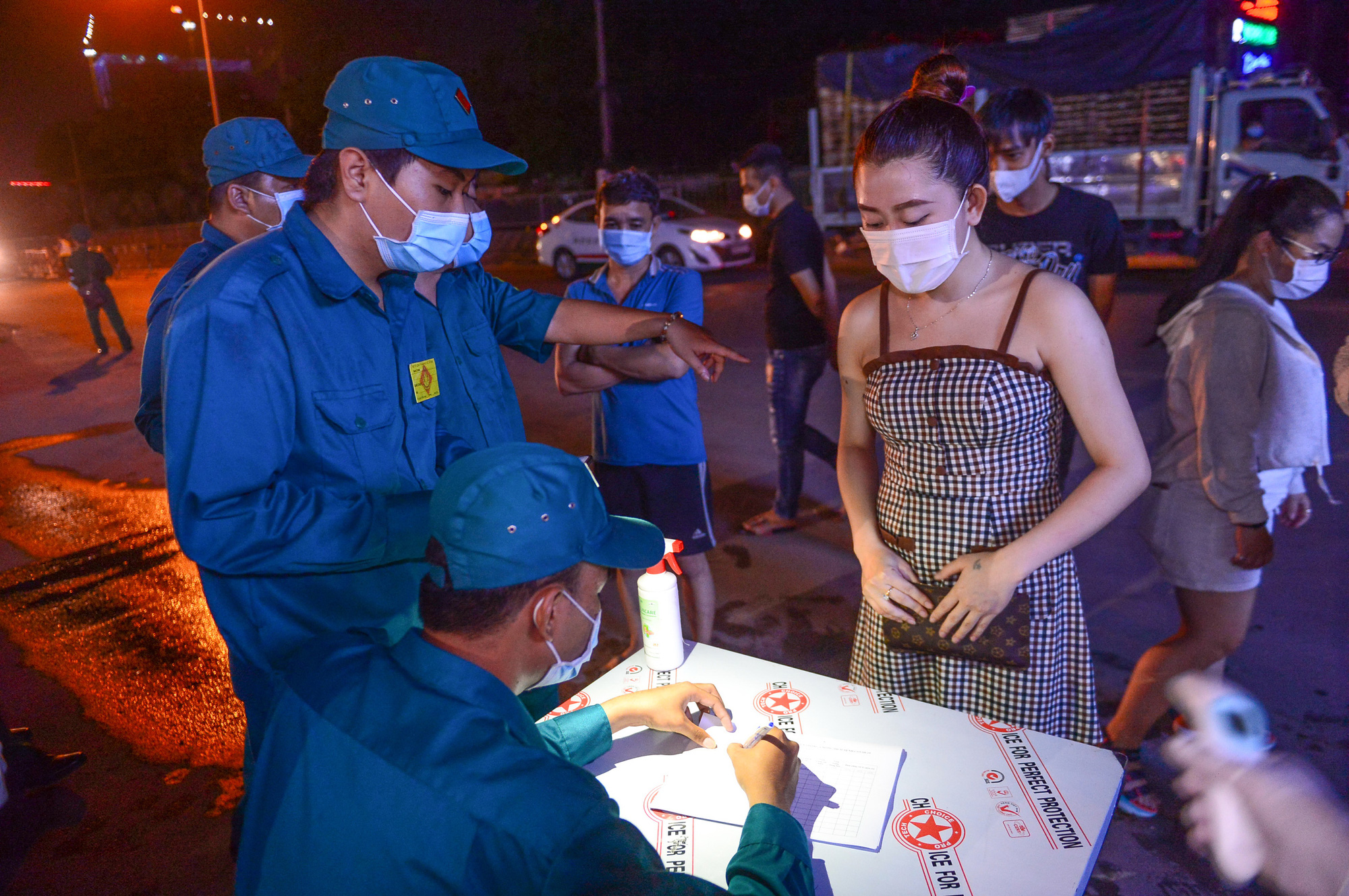 People fill in health declarations at a COVID-19 checkpoint in Ho Chi Minh City. Photo: Quang Dinh / Tuoi Tre