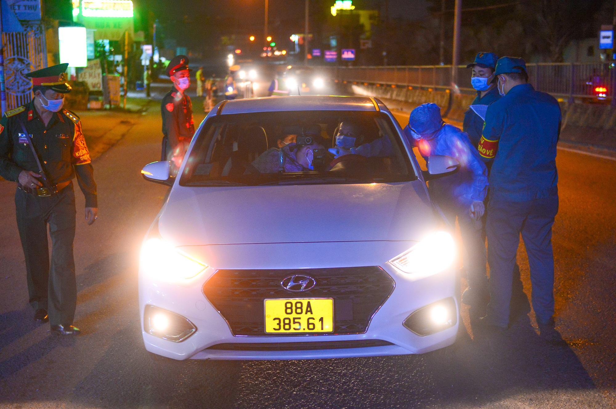 Travelers on an automobile have their body temperature measured at a COVID-19 checkpoint in Ho Chi Minh City. Photo: Quang Dinh / Tuoi Tre