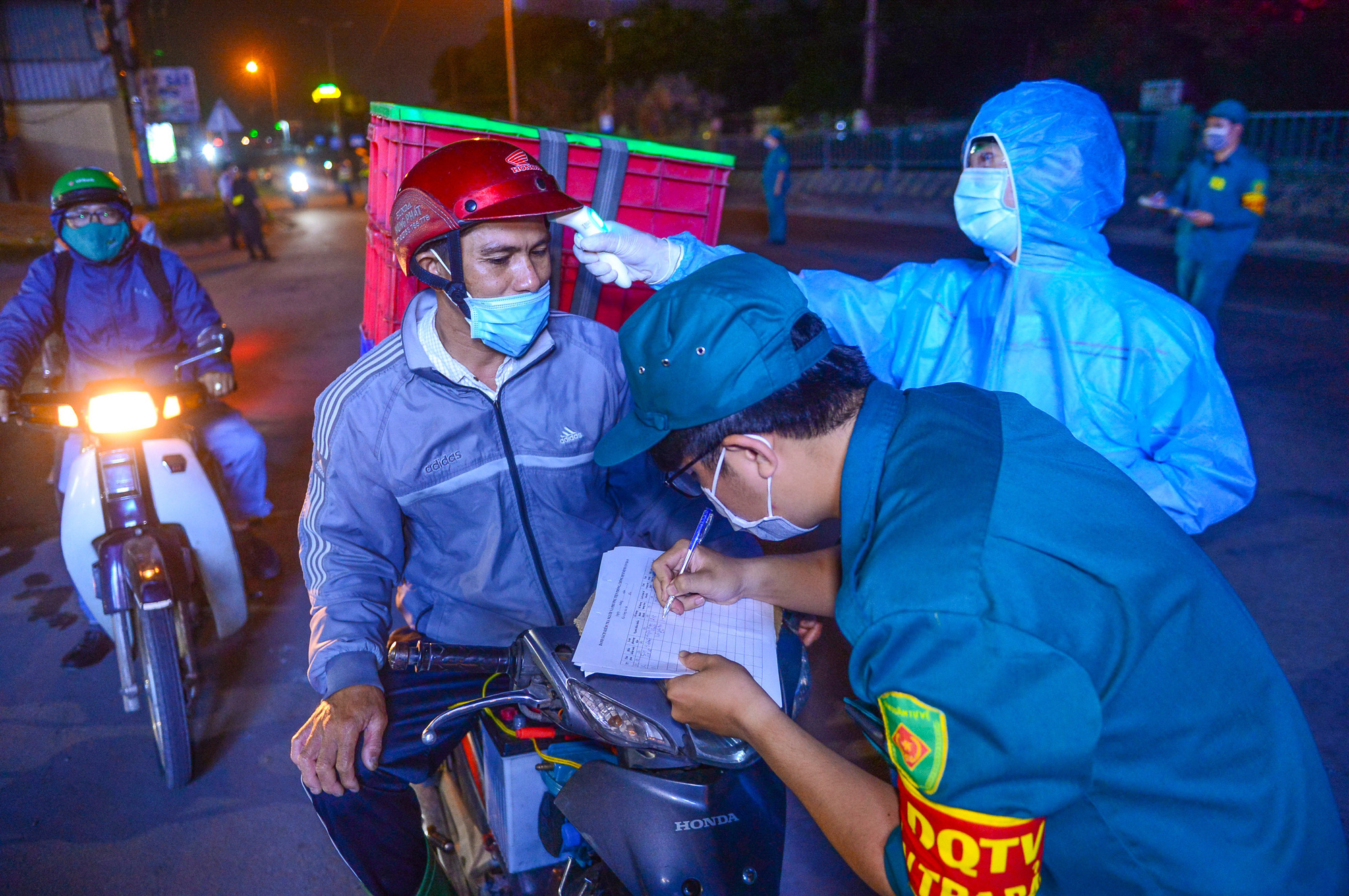 A motorcyclist has his body temperature measured at a COVID-19 checkpoint in Ho Chi Minh City. Photo: Quang Dinh / Tuoi Tre