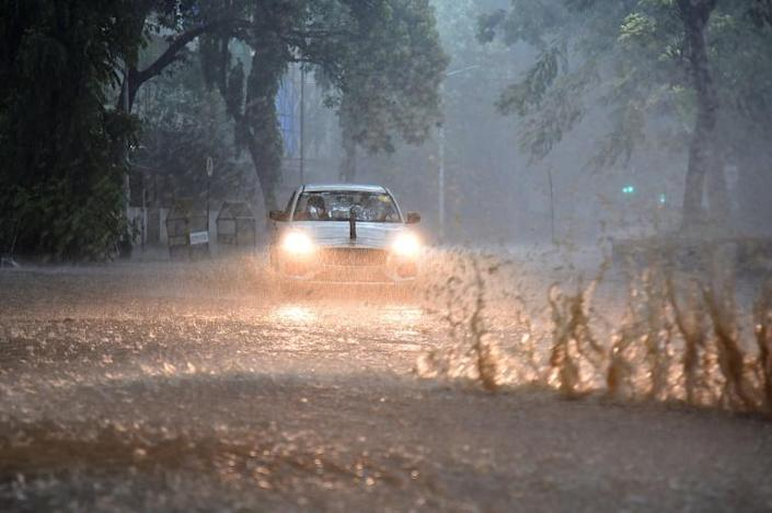 Commuters drive through a waterlogged road amidst heavy rains in Mumbai. Photo: AFP