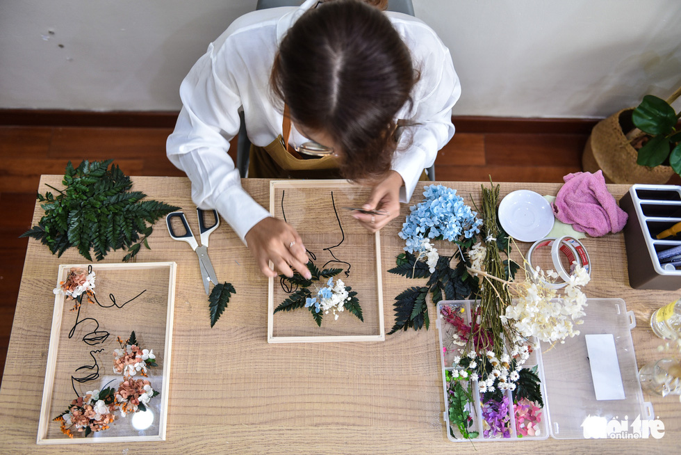 Tran Thi Phuong Trinh makes pressed flower display following a procedure she took half a year to develop.  Photo: Ngoc Phuong/Tuoi Tre