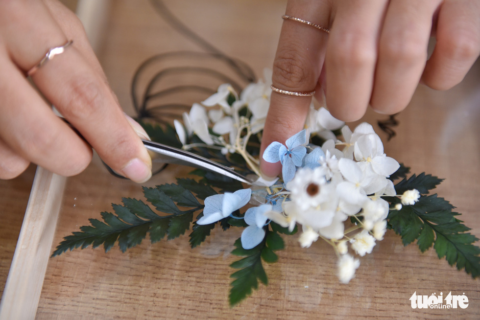 The arrangement of flowers and leaves has to be meticulously conducted. – Photo: Ngoc Phuong/Tuoi Tre