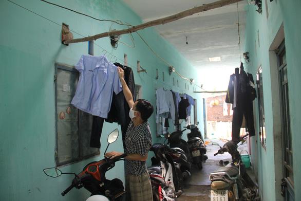 Nguyen Van Giang prepares his wife's work uniform. Photo: Truong Trung/Tuoi Tre