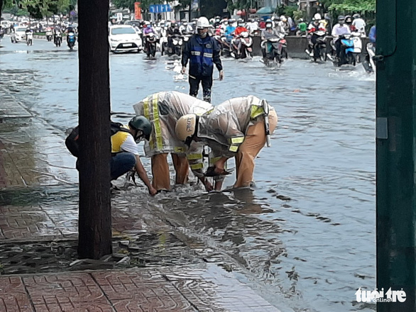 Traffic police officers help unclog a drain in Thu Duc City, Ho Chi Minh City, Vietnam on May 19, 2021. Photo: Ngoc Ha / Tuoi Tre