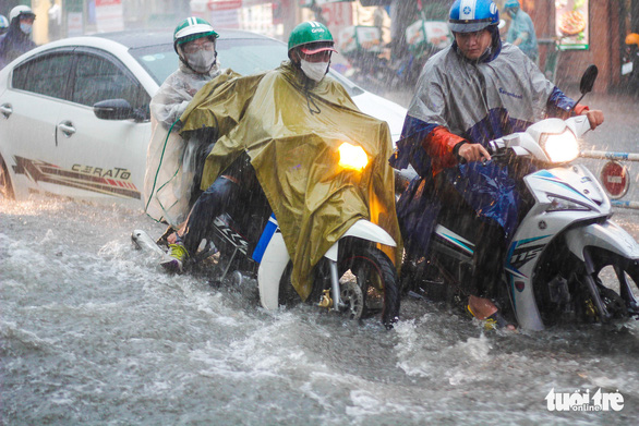 Commuters navigate a flooded street in Thu Duc City, Ho Chi Minh City, Vietnam on May 19, 2021. Photo: Chau Tuan / Tuoi Tre