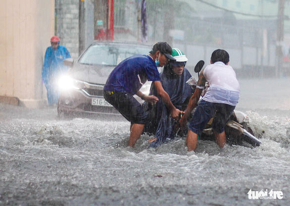 Local residents help a commuter lift his fallen motorbike amidst a flooded street in Thu Duc City, Ho Chi Minh City, Vietnam on May 19, 2021. Photo: Chau Tuan / Tuoi Tre