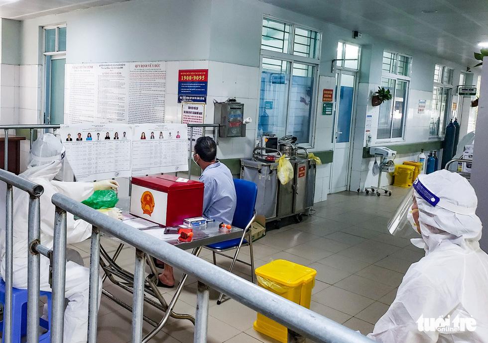 A quarantined voter reads candidates' profiles before casting his ballot at Makeshift Hospital No.1, Bac Ninh Province, VIetnam, May 22, 2021.