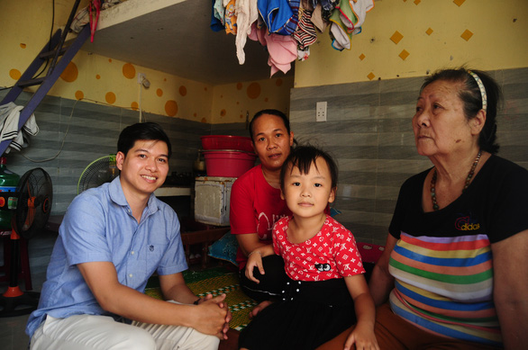 Anh (left) takes a picture with tenants of the House of Hope. – Photo: Thai Ba Dung/Tuoi Tre