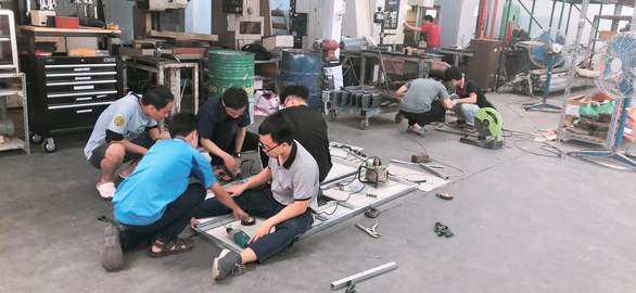 Members of BK M.C.E work on their COVID-19 screening system. Photo: Thy Huyen / Tuoi Tre