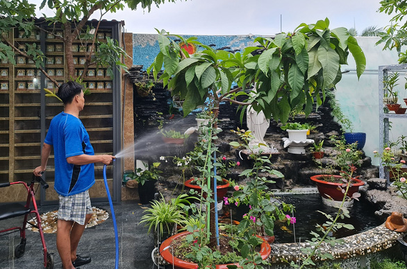 A patient waters plants in the house's garden. – Photo: Cong Trieu/Tuoi Tre