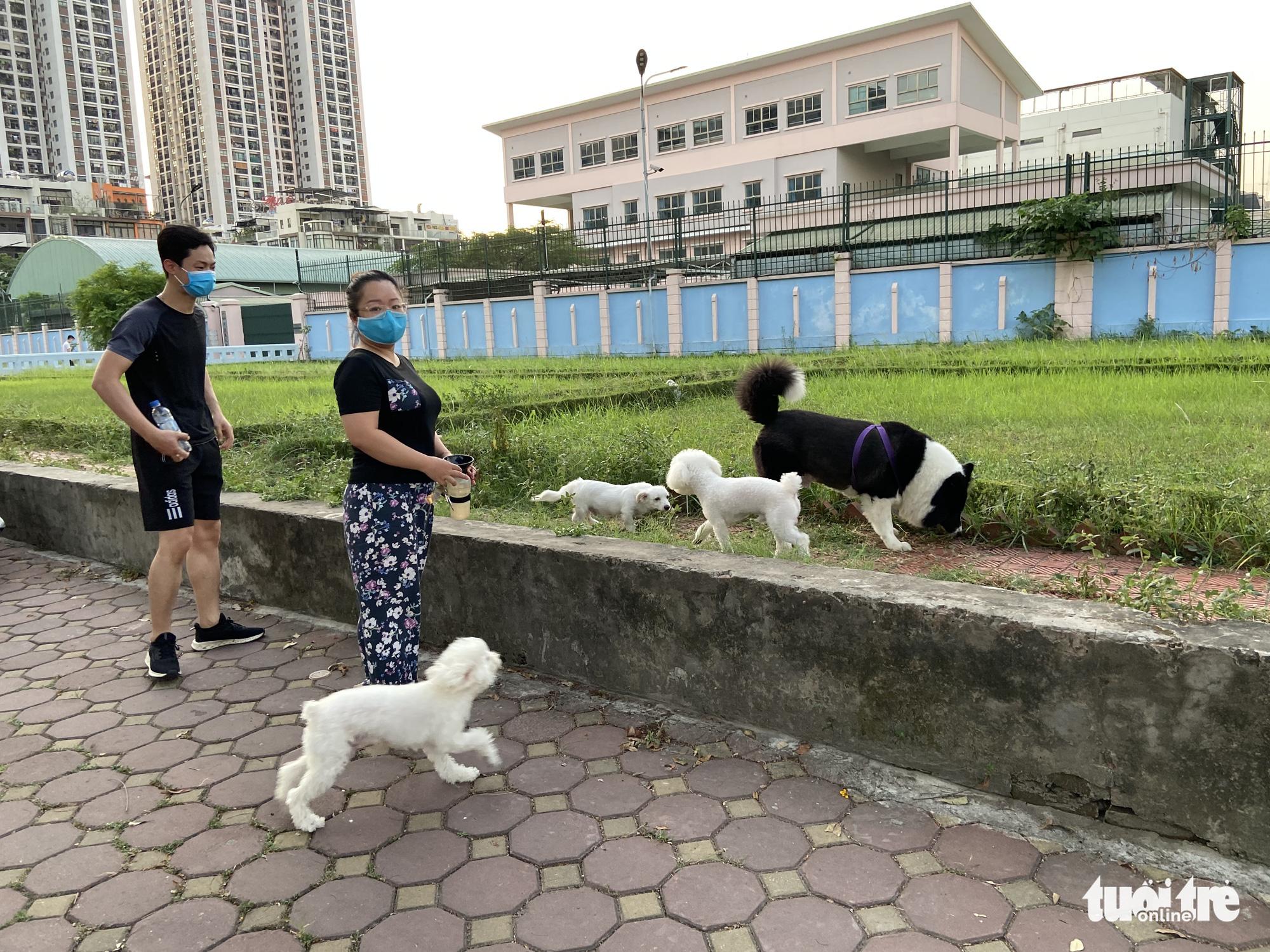 People walk pets on a sidewalk in Nam Tu Liem District, Hanoi, May 30, 2021. Photo: Q.T. / Tuoi Tre