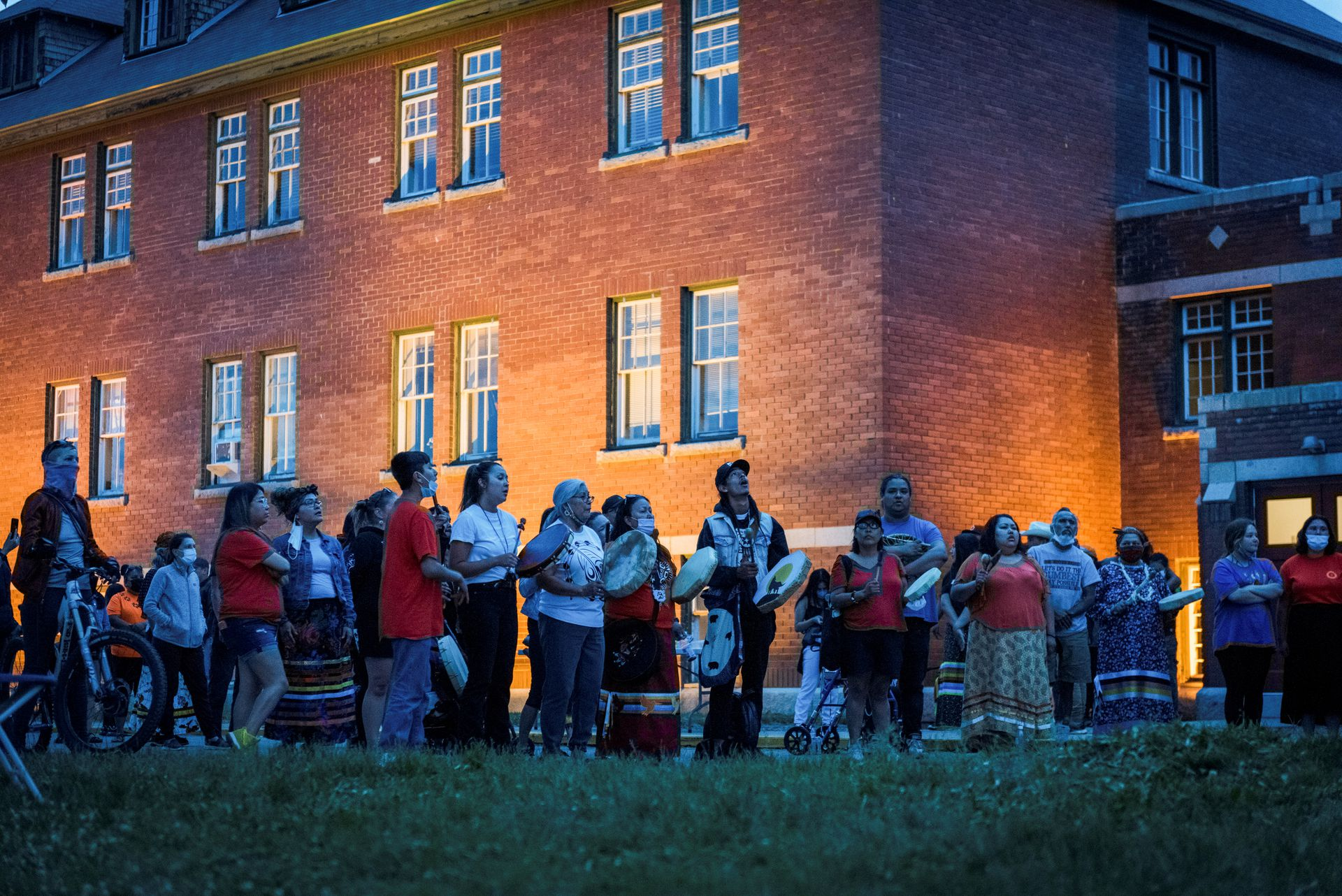 Kamloops residents and First Nations people gather to listen to drummers and singers at a memorial in front of the former Kamloops Indian Residential School after the remains of 215 children, some as young as three years old, were found at the site last week, in Kamloops, British Columbia, Canada May 31, 2021. Photo: Reuters