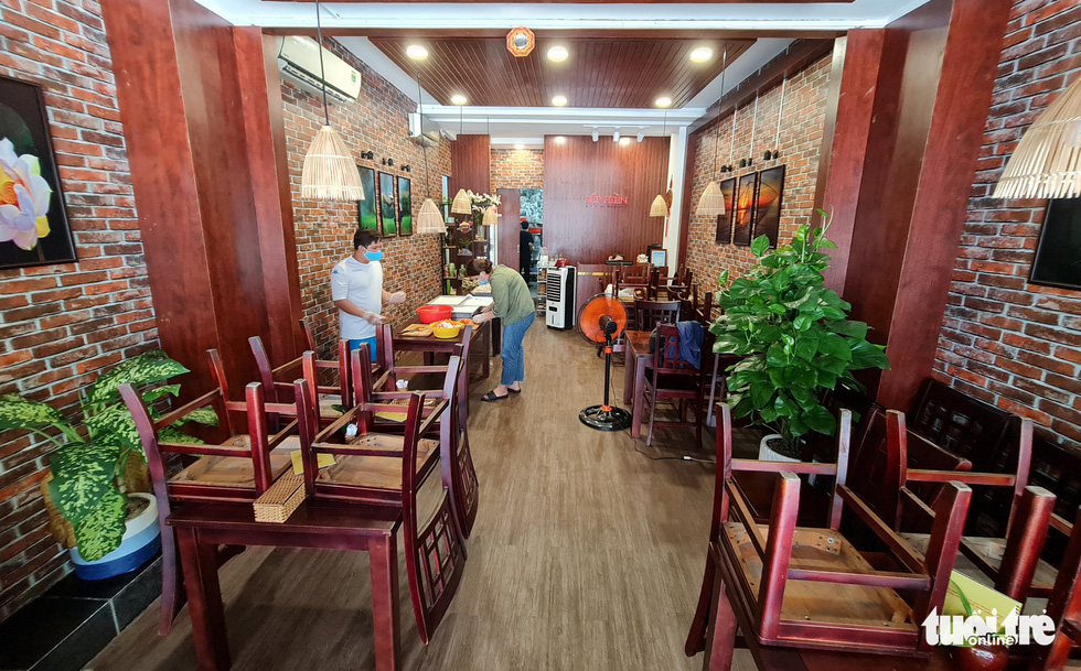 Tables and chairs must be stacked neatly as Pham Minh Hien's restaurant just sells takeout during the COVID-19 pandemic. Photo: Cong Trieu / Tuoi Tre