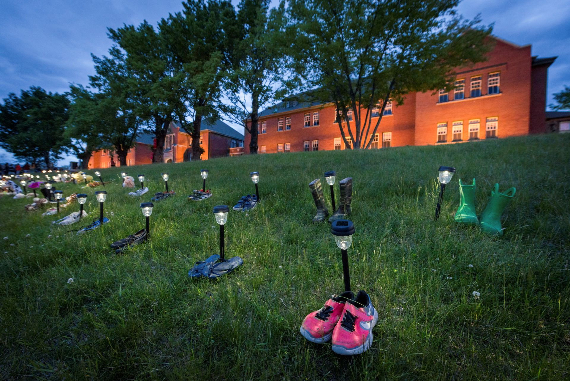 Pairs of children's shoes and toys are seen at memorial in front of the former Kamloops Indian Residential School after the remains of 215 children, some as young as three years old, were found at the site last week, in Kamloops, British Columbia, Canada May 31, 2021. Photo: Reuters