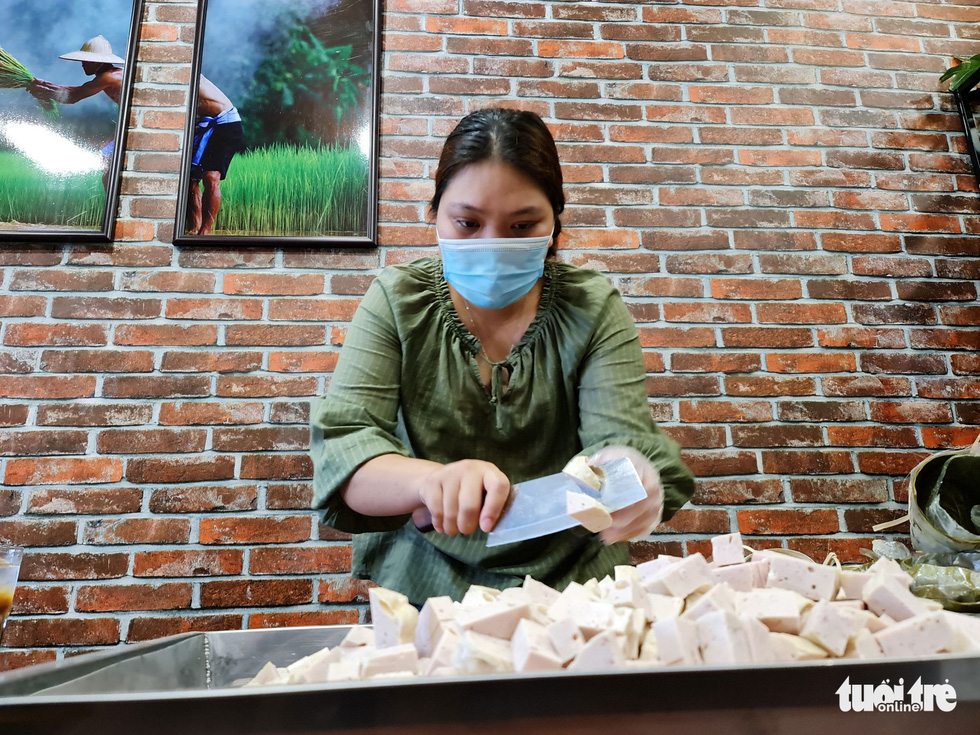 Yen Anh, 33, a resident in Go Vap District, prepares pork bologna she contributed to Pham Minh Hien's initiative of making free meals. Photo: Cong Trieu / Tuoi Tre