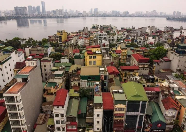 This photograph taken on June 8, 2021 shows a street vendor walking past narrow residential houses, known as 'nha ong' in Vietnamese or 'tube houses', in an urban area of Hanoi. Photo: AFP