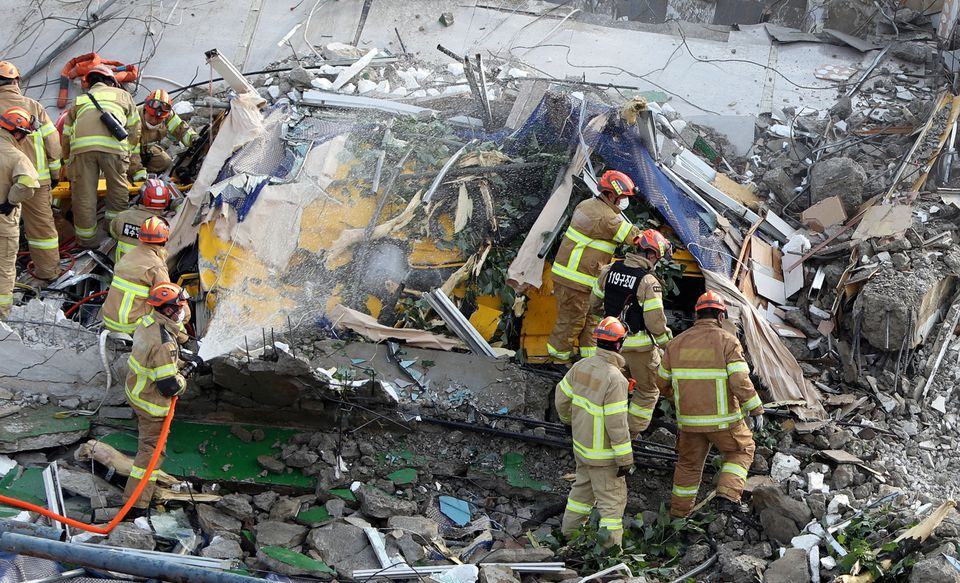 South Korean firefighters search for passengers from a bus trapped by the debris of a collapsed building in Gwangju, South Korea, June 9, 2021. Yonhap via Reuters