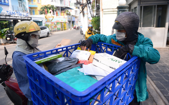 A delivery worker sends packages for a customer in Ho Chi Minh City. Photo: Q.Dinh / Tuoi Tre