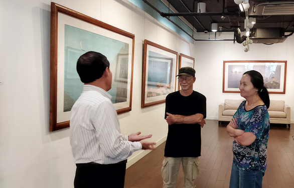 Artist Hoang Minh Hang talks with her two friends, the artist Le Dan (left) and the sculptor Tran Luan Tin at Eight Gallery in Ho Chi Minh City during her third solo exhibition in the city on March 24, 2021. Photo: Kim Thoa / Tuoi Tre