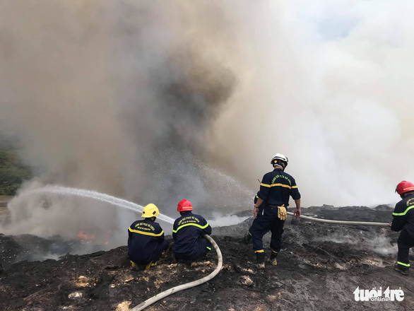 Fire policemen use water hoses to put out a landfill fire in Lien Chieu Ward, Da Nang City, Vietnam. Photo: Huy Linh / Tuoi Tre