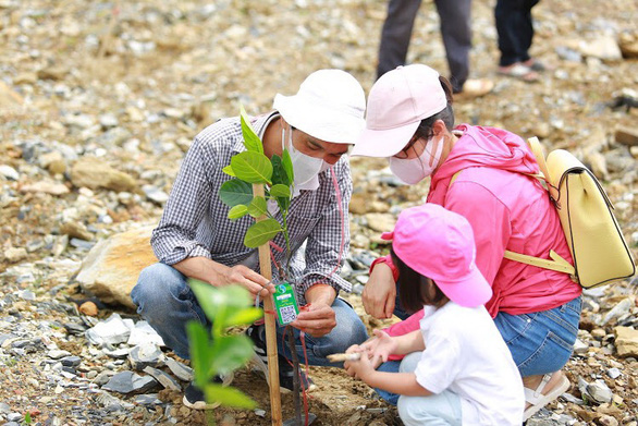 A young family participates in a weekend forest planting event. Photo: Tam An/Tuoi Tre