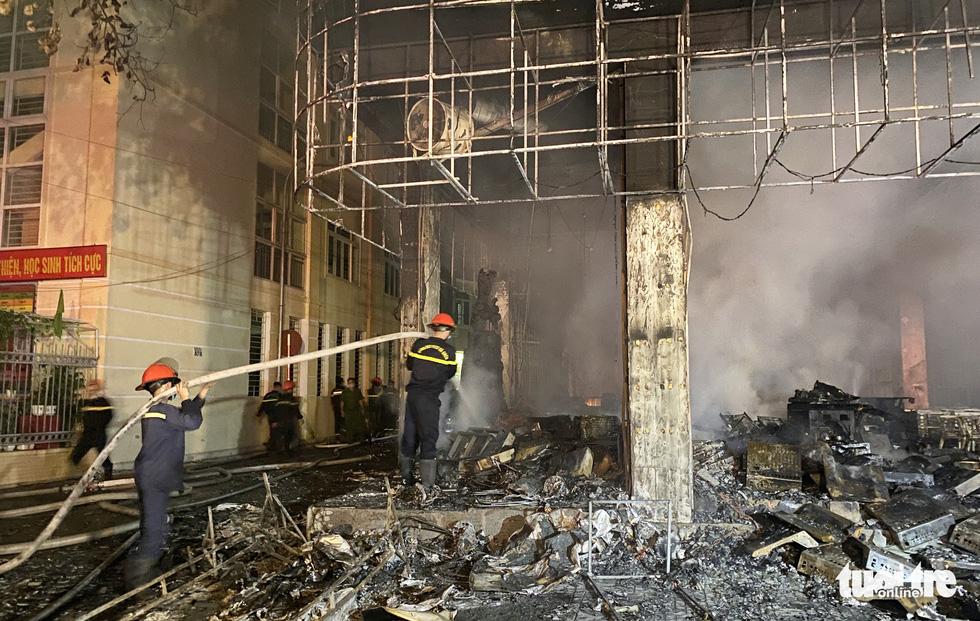Firefighters are seen extinguishing the blaze at the tea house. Photo: Doan Hoa / Tuoi  Tre