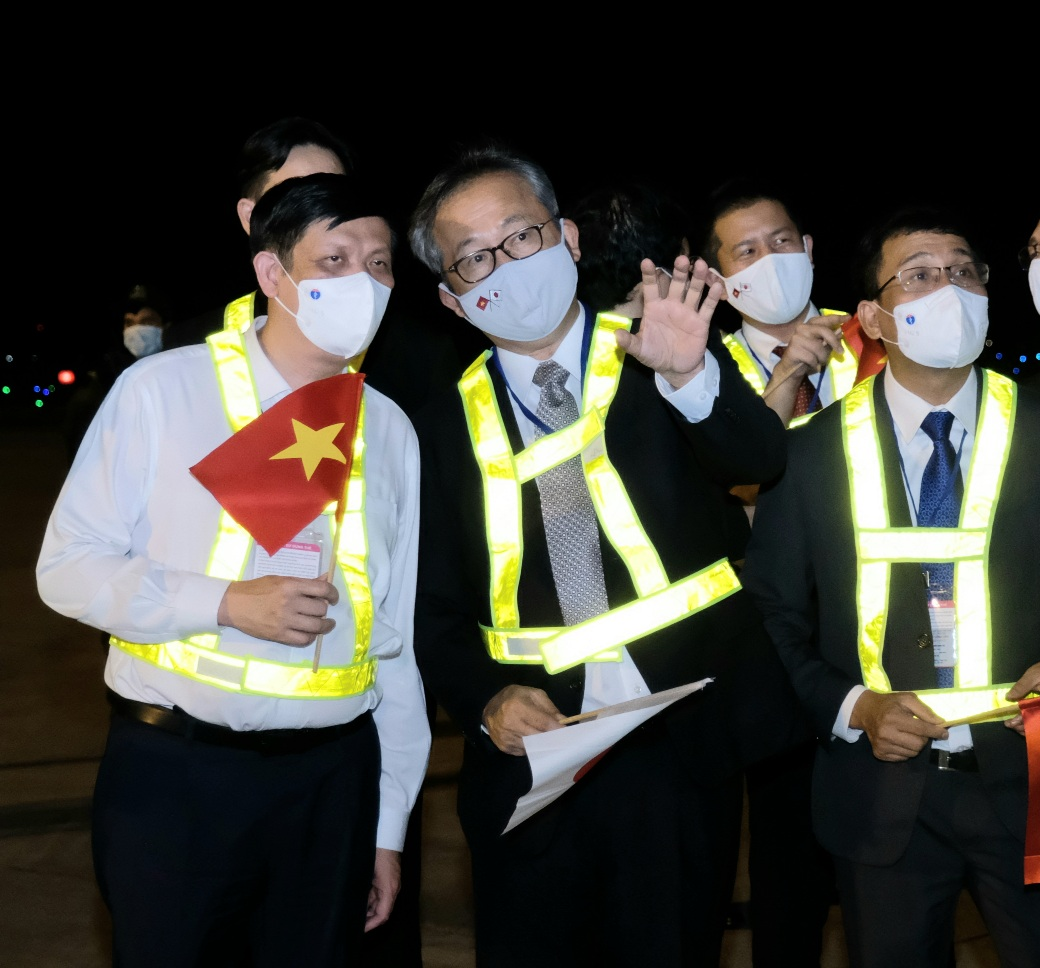Vietnamese Minister of Health Nguyen Thanh Long (left) and Japanese Ambassador to Vietnam Yamada Takio (center) wait for the arrival of AstraZeneca COVID-19 vaccine doses from Japan at Noi Bai International Airport in Hanoi, June 16, 2021. Photo: Ministry of Health