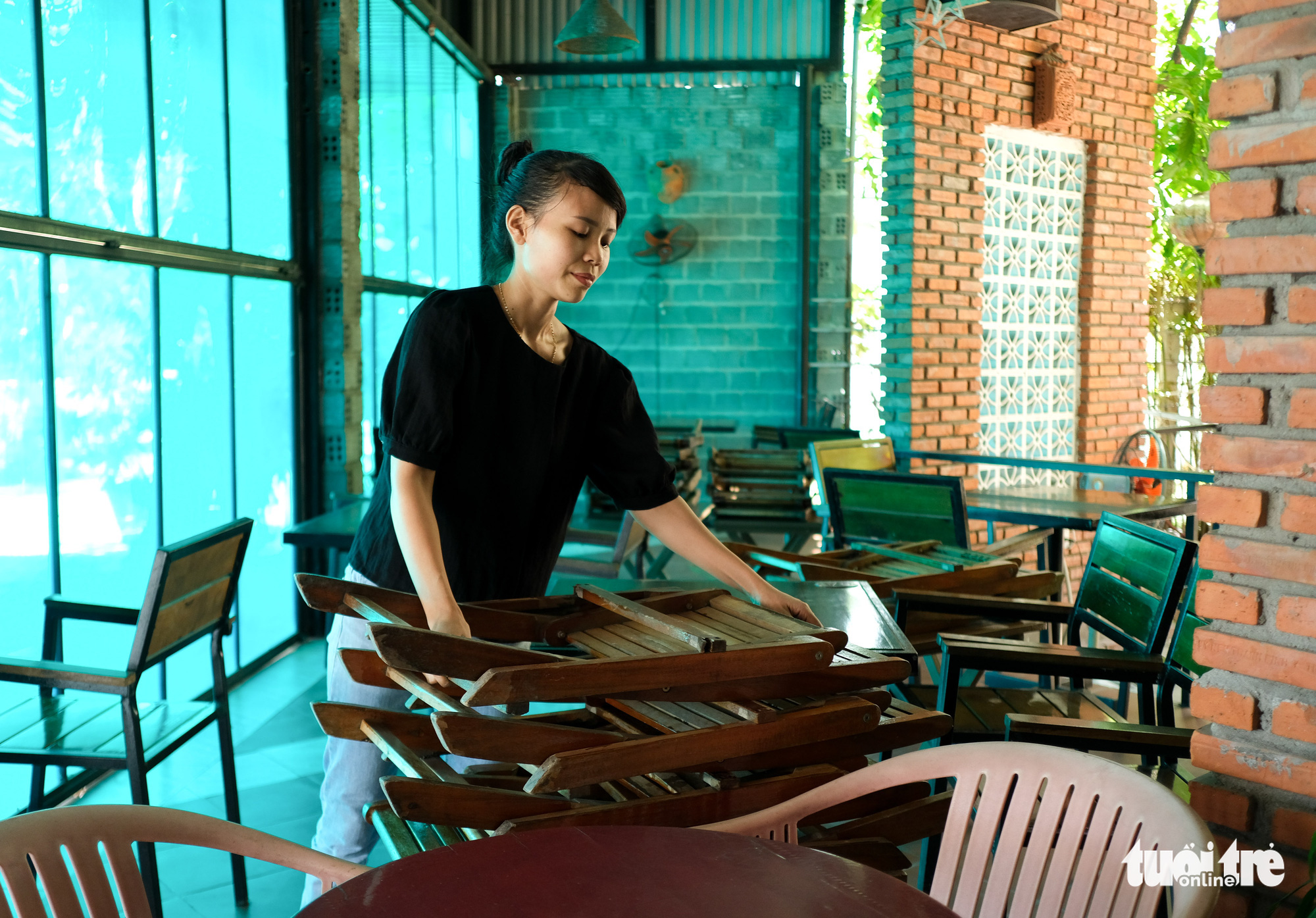 A woman puts away tables and chairs at a café in Da Nang City, June 20, 2021. Photo: Tan Luc / Tuoi Tre
