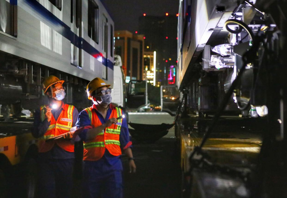 Technical workers check technical safety before the transportation of the fourth train for Ho Chi Minh City's metro line No. 1 to the Long Binh Depot in Thu Duc City, June 21, 2021. Photo: Nhat Thinh / Tuoi Tre