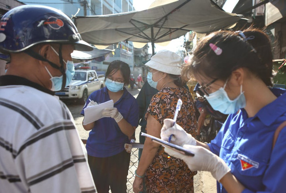 Volunteers help residents file medical declarations before entering Nguyen Dinh Chieu Market, Phu Nhuan District, Ho Chi Minh City, June 20, 2021. Photo: Nhat Thinh / Tuoi Tre