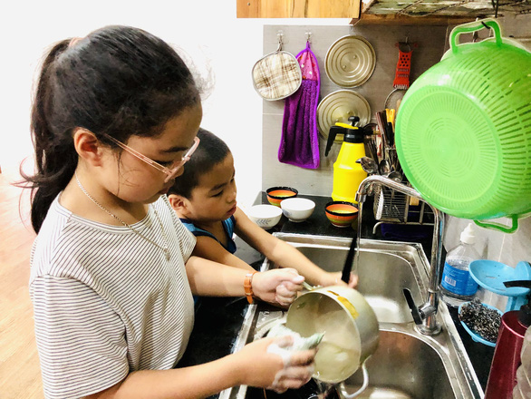 Bich Quan and her brother wash dishes together. – Photo: Phuong Chi/Tuoi Tre
