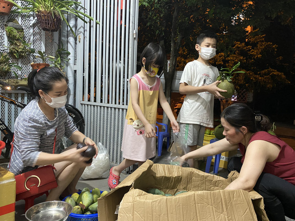 Xuan's children help their mother sort fruits. – Photo: HX/Tuoi Tre
