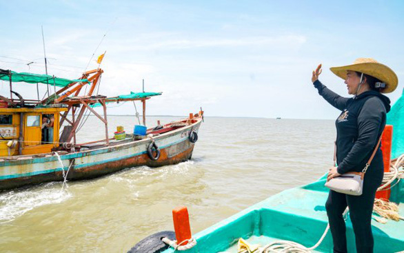 Phuong waves at a fisherman. She is loved by her fellows. Photo: Huynh Lam/Tuoi Tre