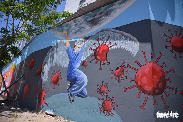 """A metaphor of a nurse """"angel"""" protecting the Earth from SARS-CoV-2 is seen on a mural in Tay Ho District. – Photo: Ha Quan/Tuoi Tre"""