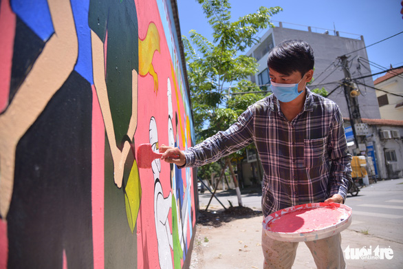 An artist resists Hanoi's hot weather to complete a mural. Photo: Ha Quan/Tuoi Tre