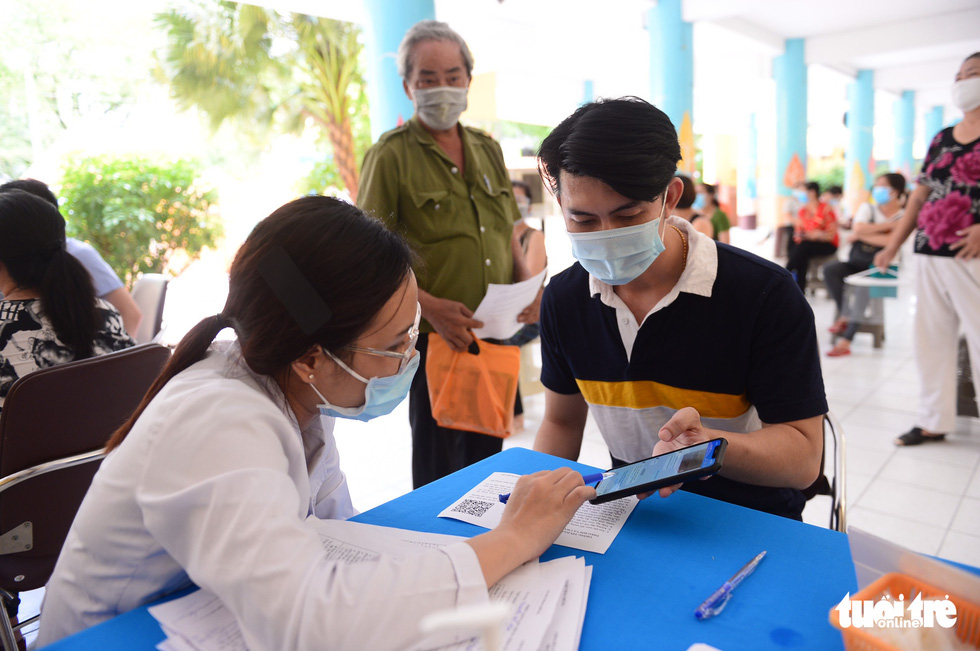 A medical worker helps a man perform health declaration on a mobile phone before COVID-19 injection at a vaccination site at Nguyen Binh Khiem Elementary School in District 1, Ho Chi Minh City, June 22, 2021. Photo: Quang Dinh / Tuoi Tre
